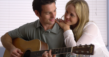 Man serenading his girlfriend with his guitar Imagens