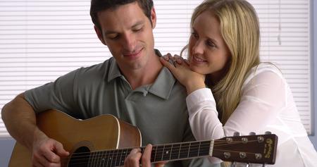 serenading: Man serenading his girlfriend with his guitar Stock Photo