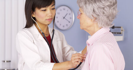 patients: Chinese doctor listening to elderly patients heart