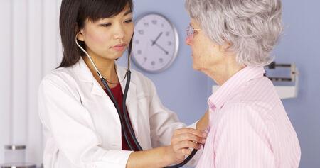 pacientes: Doctor chino que escucha el corazón del paciente de edad avanzada