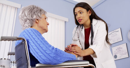 Hispanic woman doctor comforting disabled elderly patient photo
