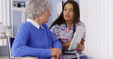 Hispanic caregiver talking with tablet with elderly patient