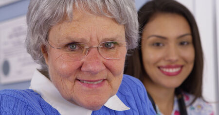 mature mexican: Cheerful elderly patient smiling with Mexican caregiver