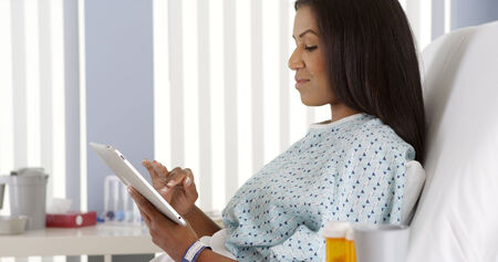 African American woman using tablet computer in hospital bed Stock Photo