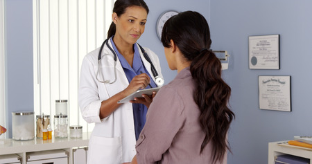 Black Primary Care Physician talking to female patient in Exam room Stock Photo