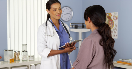 African American gynecologist talking to patient with tablet