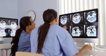 Vue arrière de deux femmes médecins travaillent ensemble sur les ordinateurs Banque d'images - 33803240