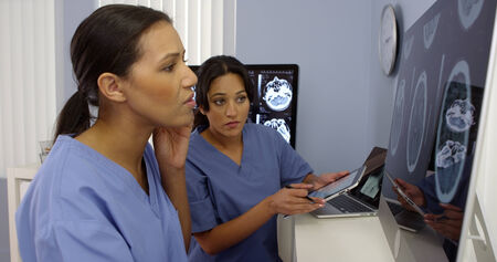 Black and hispanic female doctors working together with cell phone and computers
