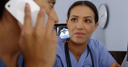 uses computer: Close up of Hispanic doctor using mobile phone while colleague uses computer