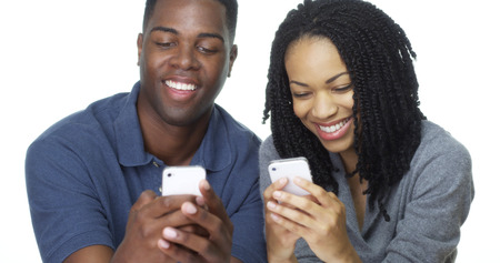 Young African American Paar SMS auf Handy zusammen Lizenzfreie Bilder