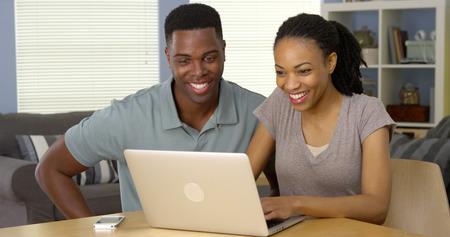 Jonge zwarte man en vrouw met behulp van laptop samen op het bureau Stockfoto