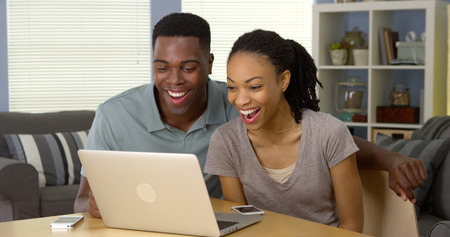 Young black couple watching funny video on laptop photo
