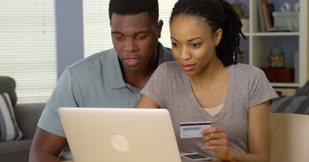 purchase: Happy African American man and woman making online purchase with credit card