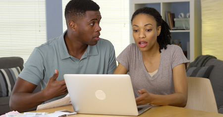 Upset young Black couple arguing over bills and finances with laptop photo