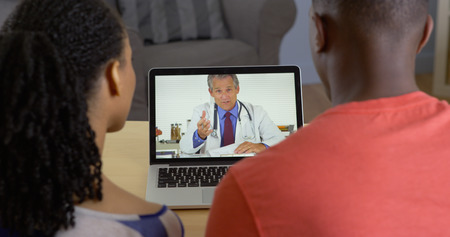 skype: Physician talking with young black couple about medical issues over internet video chat