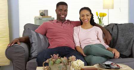 couple on couch: Happy young black couple relaxing on couch looking at camera