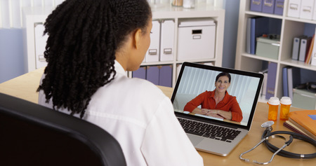 skype: Woman patient talking to female doctor over internet video chat Stock Photo