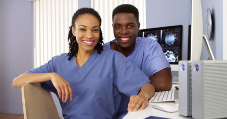nurses station: Two Black nurses in nurses station sitting at computer