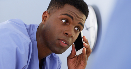 Close up of black doctor talking on cellphone and working with colleague photo