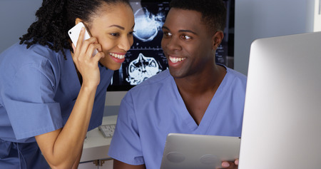 doctor computer: Black man and woman doctors working together with technology