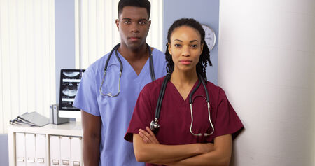 serious doctor: Portrait of two African American medical specialists standing in hospital