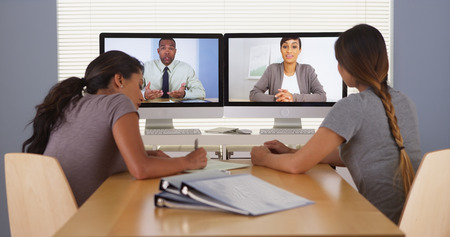 voip: Professional team of multi-ethnic business colleagues having a video conference Stock Photo