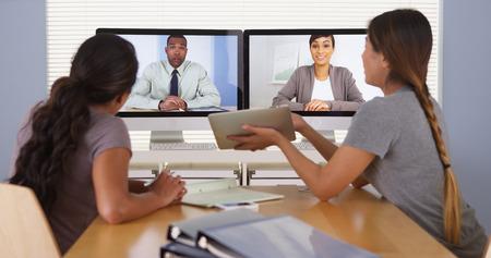 ビデオ会議を持つ多様なビジネス部門の同僚の勤勉なチーム