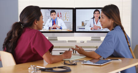 conferencing: Group of diverse medical doctors video conferencing Stock Photo