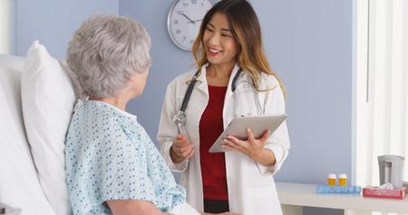 Médecin qui parlent le japonais avec patient âgé dans son lit d'hôpital Banque d'images - 33803382