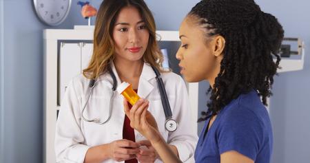 Doctor asiático explicando nueva receta para paciente negro