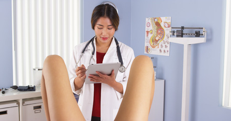 Japanese gynecologist with patient in exam room Stock Photo