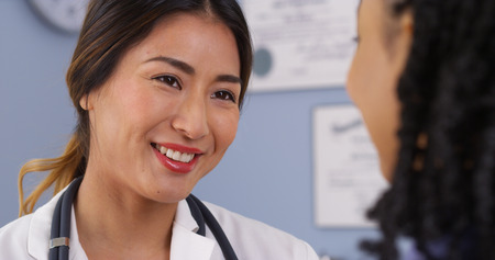 check up: Close up of happy Asian doctor looking at patient