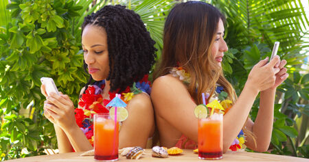 Black and Asian best friends on vacation using mobile phones photo