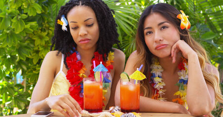ennui: Bored friends sitting at table on tropical vacation Stock Photo