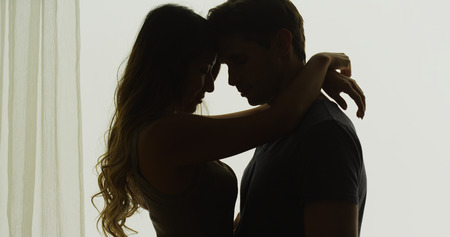 romantik: Interracial par vara intim framför fönstret