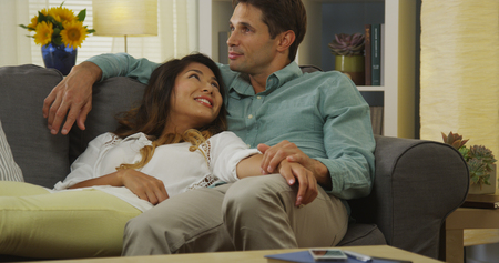 couple on couch: Interracial couple relaxing on couch