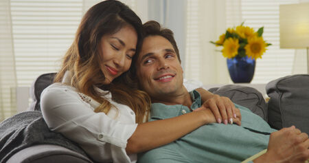 couple on couch: Affectionate interracial couple sitting on couch
