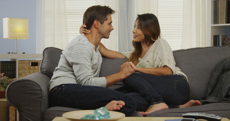 couple on couch: Affectionate mixed couple talking on couch