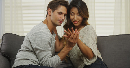 Interracial couple looking at engagement ring