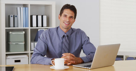 skype: Businessman sitting at desk and talking to camera with laptop