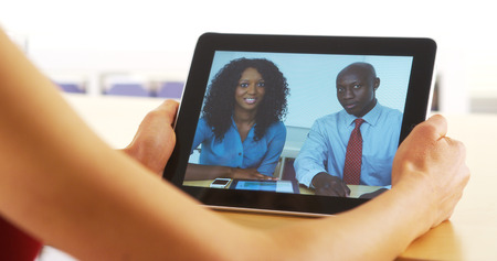 mobile voip: Closeup of black businesspeople talking on tablet