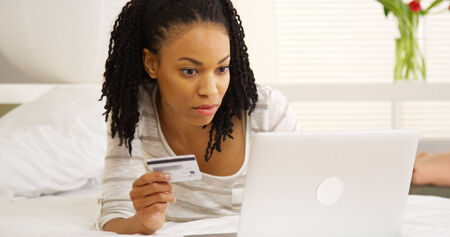 web browsing: Black woman typing in credit card number