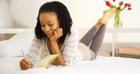 writing black: Happy black woman writing in journal Stock Photo