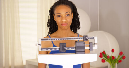 woman on scale: Disappointed black woman checks weight and walks away