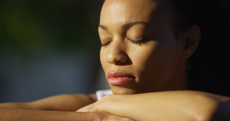 eye  closed: Black woman sitting with eyes closed outdoors Stock Photo