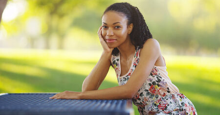 young woman sitting: Black woman sitting on a park bench smiling
