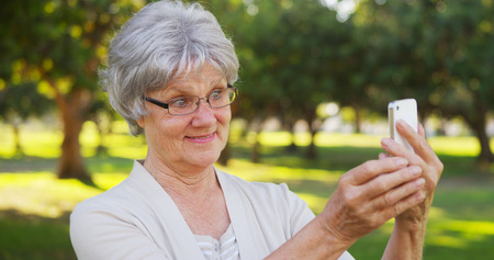 Hip grandma taking selfies at the park photo