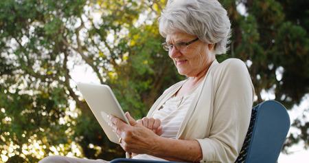 Grandma using tablet at the park Stock Photo