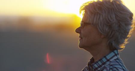 mujer mirando el horizonte: Mujer madura que se coloca en la playa Foto de archivo