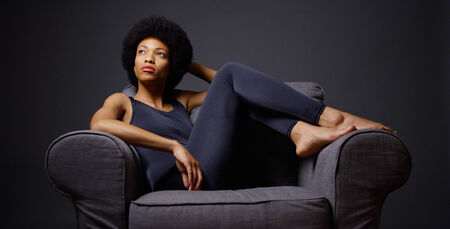 woman on couch: Black woman sitting in chair thinking